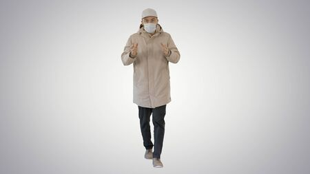 Man in winter outfit and medical mask talking to you explaining something while walking on gradient background.