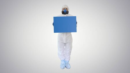 Lab scientist in safety suit holding board on gradient background.
