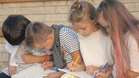 Four Kids Sitting and Painting outdoors.