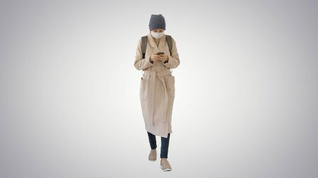 Woman dressed in a coat wearing medical mask using phone and walking on gradient background.