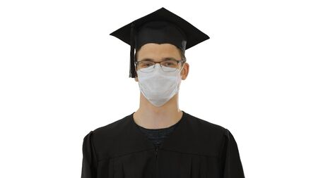 Student in gaduation gown and face mask stumbling on white background.