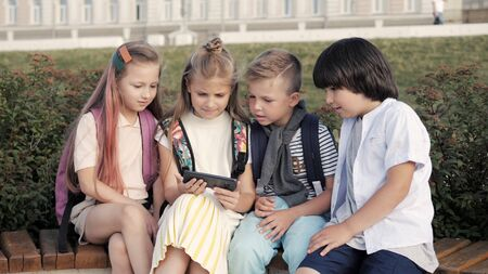 Four gadget addicted kids sitting in the park and looking into s