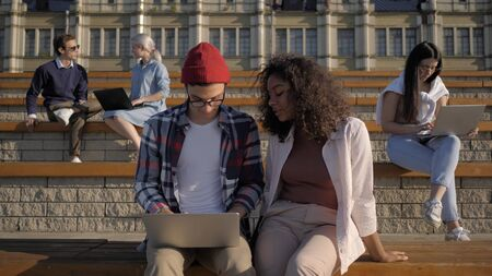 Young students working with laptop computers outdoors.