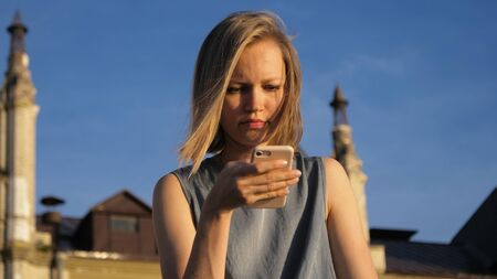 Young pretty caucasian woman sitting in park use smartphone. Imagens