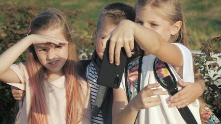 Cute pupils taking a selfie outdoors. Imagens