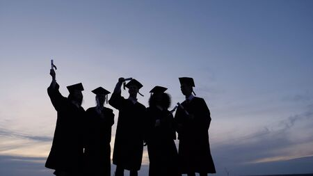 Silhouette of graduates with certificates on a sunset background 版權商用圖片