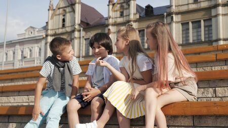 Four cute friends kids talking sitting on a bench.