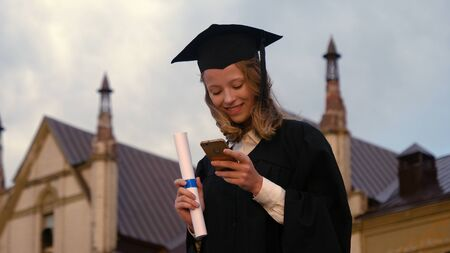 Pretty teen in graduation gown texting on cell phone. 版權商用圖片