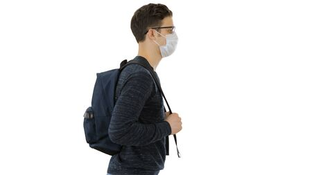 Student in protective masks walking with backpack on white background. Standard-Bild
