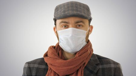 Handsome young European man in trendy coat wearing disposable protective face mask on gradient background. Standard-Bild