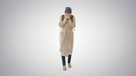 Woman in a coat walking and coughing on gradient background. Standard-Bild