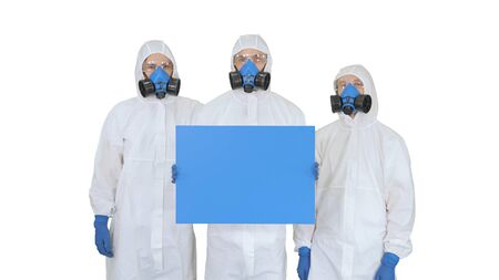 Three doctors in protective suits holding blank board on white background.