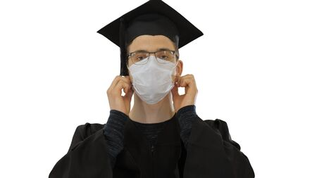 Young man with graduation gown in medical mask on white background.