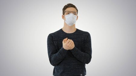 Coronavirus Man wearing protective mask cleaning his hands with sanitizer on gradient background.