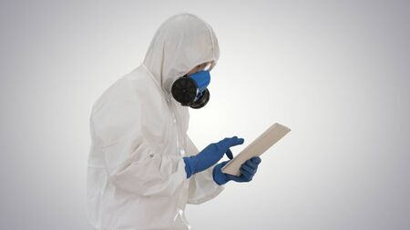 Scientist or docrot wearing biohazard suits and protective masks using digital tablet while walking on gradient background.