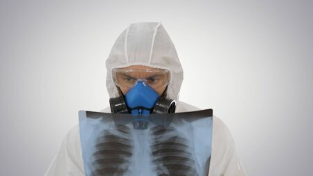 Close up. Medic in white hazmat protective suit checking lungs X-ray looking for epidemic virus on gradient background. Professional shot in 4K resolution. 53. You can use it e.g. in your medical, commercial video, business, presentation, broadcast Standard-Bild