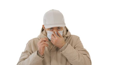 Medium shot. Man in warm coat walking and putting on medical mask on white background. Professional shot in 4K resolution. 53. You can use it e.g. in your medical, commercial video, business, presentation, broadcast Standard-Bild