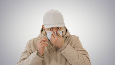 Medium shot. Man in warm coat walking and putting on medical mask on gradient background. Professional shot in 4K resolution. 53. You can use it e.g. in your medical, commercial video, business, presentation, broadcast