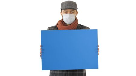 Close up. Mockup blue screen. Man in a trendy outfit and medical mask holding blank placard on white background. Professional shot in 4K resolution. 53. You can use it e.g. in your medical, commercial video, business, presentation, broadcast