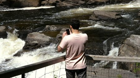 Medium shot.Man taking a picture of a waterfall on smartphone. Travel concept. Professional shot  02.