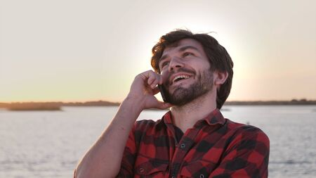 Close up. Slow motion.Young positive cheerful man talking by mobile phone at sunset. Professional shot 031.