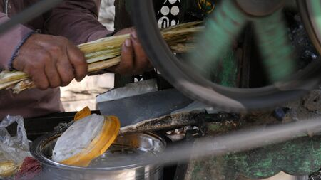 Close up.Indian worker pressing juice from sugar cane at the small rural sugar mill in India. Professional shot 024. Standard-Bild