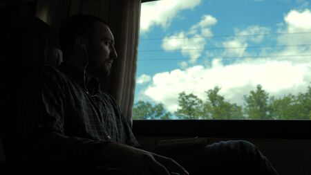 Medium shot.Young Man Listening To Music On Train Journey And Singing. Professional shot 02.