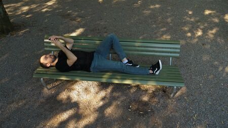 Wide shot.Handsome man lying on the bench outdoors and using smartphone. Professional shot 02. Standard-Bild