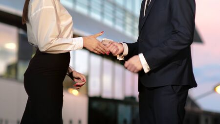 Close up.Businessman pays businesswoman in euros and they shake hands after that. Professional shot  029.