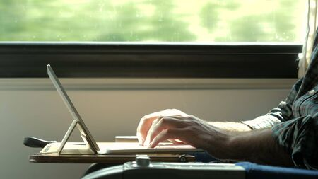 Close up.Man hands typing on laptop tablet computer in a train. Professional shot  02.