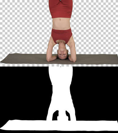 Beautiful young woman doing yoga exercise variation of supported headstand, garuda salamba sirsasana with crossed legs, Alpha Channel