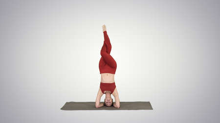 Beautiful young woman doing yoga exercise variation of supported headstand, garuda salamba sirsasana with crossed legs on gradient background.