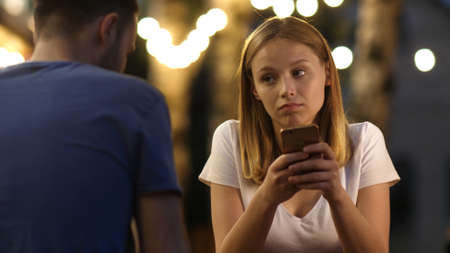 Bored teen girl on a date using the phone. Couple spending time scrolling web pages on phones.