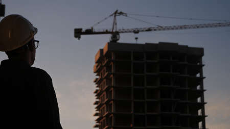Engineer or Architect wearing personal protective equipment safety helmet checks the building at sunset.