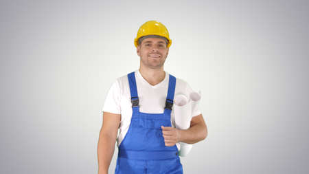 Construction worker walking with blue prints and smiling to camera on gradient background.