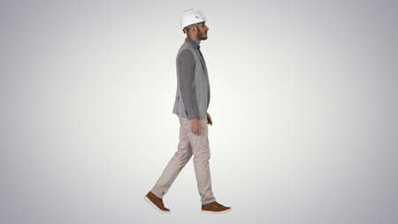 Architect in white helmet walking on gradient background.