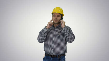 Construction worker using smartphone on gradient background.