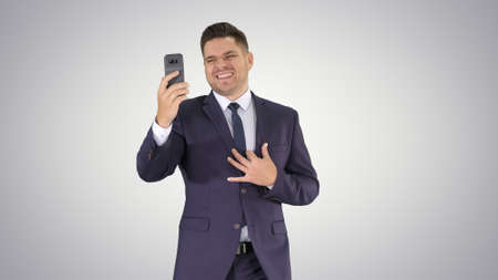 Young businessman using smartphone to videocall to business partner while walking on gradient background.