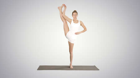 Beautiful sporty young woman in white sportswear working out idoing Utthita Hasta Padangustasana, Extended Hand to Big Toe pose on gradient background.