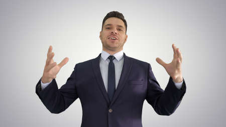 Man in formal clothes speaking to camera doing hand gestures in a very expressive and positive way on gradient background.