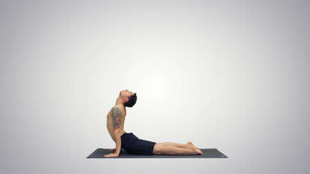 Flexible strong yoga man in Upward and Downward Facing Dog Urdhva Mukha Svanasana on gradient background.