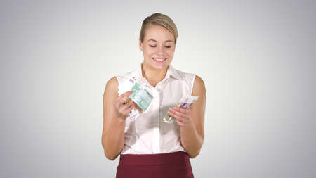 Beautiful joyful girl with Euro bills on gradient background.