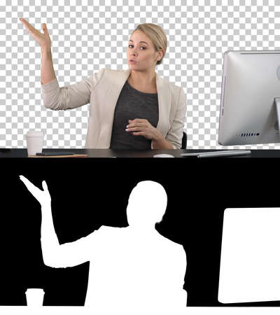 Lady looking and talking to camera at her work desk and pointing to the sides, Alpha Channel