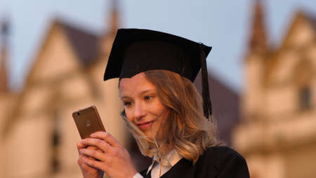 Young cute student graduate texting message on her phone. Zdjęcie Seryjne
