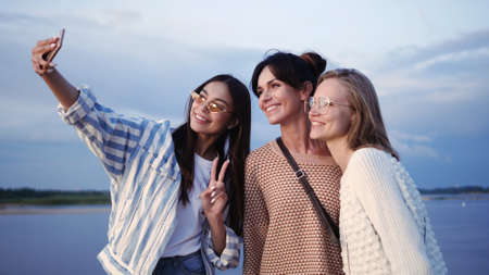 Three young smiling women taking selfie photos on smartphone. Zdjęcie Seryjne