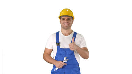 Worker with wrench showing thumb up and smiling to camera on white background.