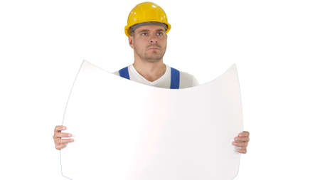 Thoughtful builder in helmet looking at blueprint and walking on white background.