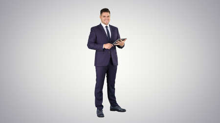 Expressive young businessman with tablet presenting something swiping on gradient background.