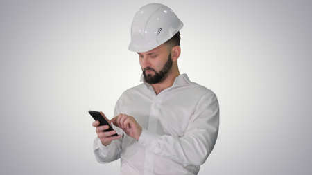 Smart engineer in white shirt and safety engineering hat using s