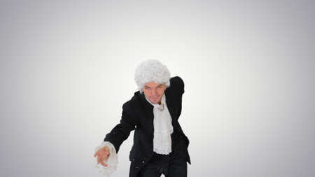 Man in old-fashioned laced frock coat and white wig making a bow Foto de archivo